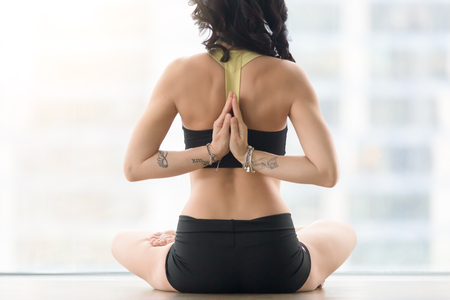 Young attractive woman practicing yoga, sitting in Ardha Padmasana exercise, Half Lotus pose with namaste behind the back, working out, wearing sportswear, black tank top, shorts, rear view Stock Photo