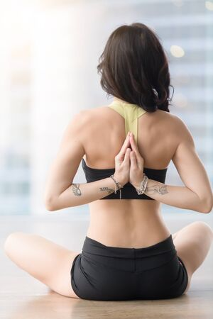 Young attractive woman practicing yoga, sitting in Ardha Padmasana exercise, Half Lotus pose with namaste behind back, working out, wearing sportswear, black tank top, shorts, near window, rear view Stock Photo