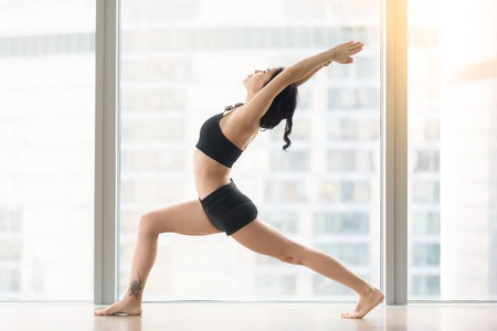 Young sporty woman practicing yoga, standing in Warrior I exercise, Virabhadrasana one pose, working out, wearing sportswear, black tank top, shorts, full length, near floor window with city view