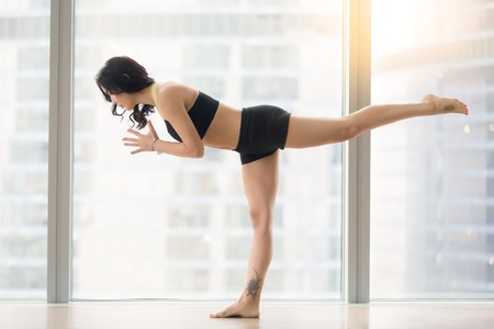 Young attractive woman practicing yoga, standing in Warrior III, Virabhadrasana three pose, working out, wearing sportswear, black tank top, shorts, full length, near floor window, city view