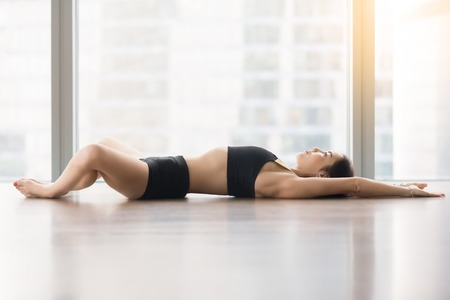 Young sporty woman practicing yoga, lying in Reclined Butterfly exercise, supta baddha konasana pose, working out, wearing sportswear, black tank top, shorts, full length, floor window with city view Stock Photo