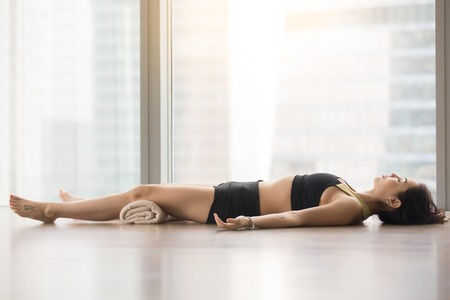 Young sporty woman practicing yoga, lying in Corpse, Dead Body exercise, Savasana pose, working out, wearing sportswear, black tank top, shorts, indoor full length, near floor window with city view Stock Photo
