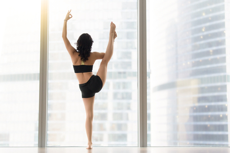 Woman practicing yoga, standing in Utthita Hasta Padangustasana exercise, Variation of Extended Hand to Big Toe pose, working out, wearing black tank top, shorts, full length, near window, rear view