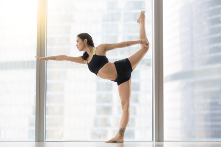 Young attractive woman practicing yoga, standing in Natarajasana exercise, Lord of the Dance pose, working out, wearing sportswear, black tank top, shorts, indoor full length, floor window with city