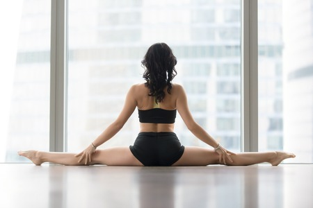 Young sporty woman practicing yoga, sitting in Samakonasana exercise, Straight Angle pose, working out, wearing sportswear, black tank top, shorts, indoor full length, against floor window, rear view