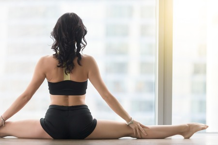 Young sporty woman practicing yoga, sitting in Samakonasana exercise, Straight Angle pose, working out, wearing sportswear, black tank top, shorts, indoor, floor window with city, rear view, closeup