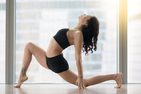 Young sporty woman practicing yoga, standing in anjaneyasana exercise, Horse rider pose, working out, wearing sportswear, black tank top, shorts, indoor full length, near floor window with city view Stock Photo