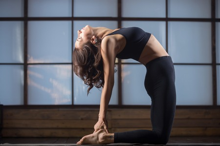 ushtrasana: Young attractive woman practicing yoga, standing in Camel exercise, Ustrasana pose, working out, wearing sportswear, black tank top, pants, indoor full length, studio evening practice
