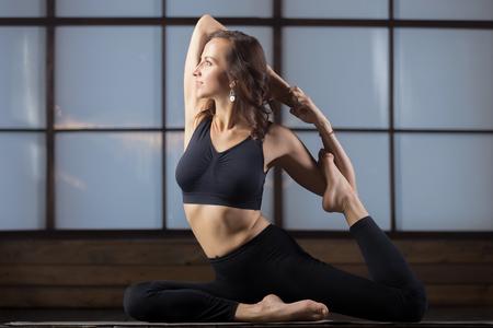pada: Young attractive woman practicing yoga, sitting in Mermaid exercise, Eka Pada Rajakapotasana pose, working out, wearing sportswear, black tank top, pants, indoor full length, studio evening practice
