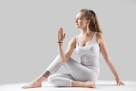 Young attractive woman practicing yoga, sitting in Ardha Matsyendrasana exercise, Half lord of the fishes pose, working out, wearing sportswear, white tank top, pants, indoor full length, grey studio Stock Photo