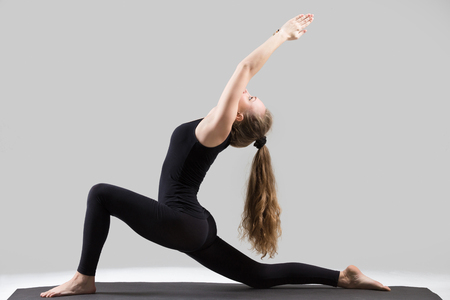 Young attractive yogi woman practicing yoga, stretching in Horse rider exercise, anjaneyasana pose, working out, wearing sportswear, black tank top, pants, indoor full length, isolated, grey studio