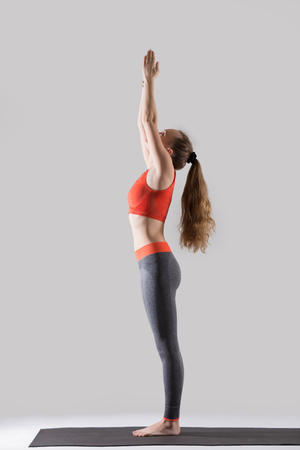 Young attractive woman practicing yoga, standing in Tadasana exercise, mountain pose, working out, wearing sportswear, red tank top, pants, indoor full length, isolated against grey studio background