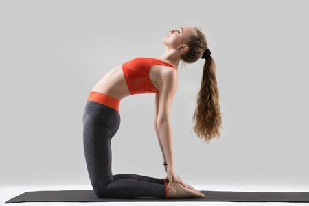 Young attractive woman practicing yoga, stretching in Ustrasana exercise, Camel pose, working out, wearing sportswear, red sports bra, pants, indoor full length, isolated, grey studio background