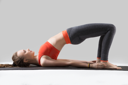 Young happy attractive woman practicing yoga, doing dvi pada pithasana exercise, Glute Bridge pose, working out, wearing sportswear, red tsports bra, pants, indoor full length, isolated, grey studio