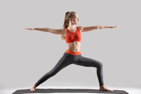 Young attractive yogi woman practicing yoga, standing in Warrior Two exercise, Virabhadrasana II pose, working out, wearing sportswear, red sports bra, pants, indoor full length, isolated, grey studio