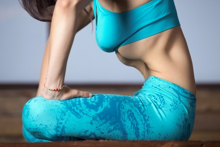Young attractive woman practicing yoga, making Upward Abdominal Lock, Uddiyana Bandha, sitting in Half Lotus pose, working out, wearing sportswear, blue tank top, pants, evening practice, close up