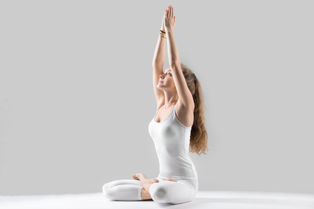 Young attractive woman practicing yoga, sitting in Padmasana exercise, Lotus pose, working out, wearing sportswear, white tank top, pants, indoor full length, isolated against grey studio background