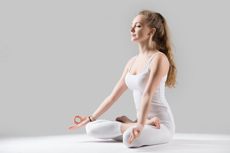 Young attractive woman practicing yoga, sitting in Padmasana exercise, Lotus pose on meditation session, working out wearing sportswear white tank top, full length, isolated, grey studio, closed eyes