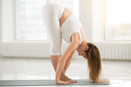 to bend: Young attractive woman practicing yoga, standing forward bend in head to knees exercise, uttanasana pose, working out, wearing sportswear, sport bra, pants, indoor full length, white color background
