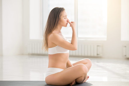 siddhasana: Young lady practicing yoga, sitting in Easy Seat pose, making Alternate Nostril Breathing exercise, using nadi shodhana pranayama technique, working out indoor, white room background, full length