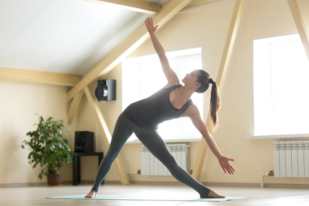 Young attractive woman practicing yoga, standing in variation of extended triangle exercise, Utthita Trikonasana pose, working out, wearing grey sportswear, indoor full length, home background
