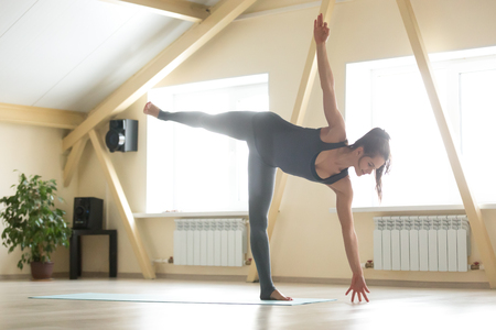 chandrasana: Young attractive happy woman practicing yoga, standing in Ardha Chandrasana exercise, Half Moon pose, working out wearing sportswear, grey tank top, pants, indoor full length, home interior background Stock Photo