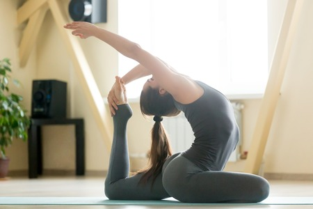 eka: Young attractive woman practicing yoga, stretching in One Legged King Pigeon exercise, Eka Pada Rajakapotasana pose, working out, wearing sportswear, grey tank top, pants, indoor full length, room Stock Photo