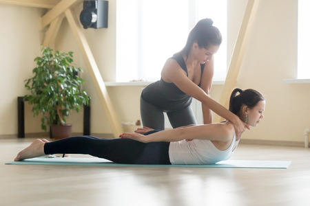 Young beautiful lady beginning yoga practice with private teacher at home class, working out with professional female yogi instructor. Trainer helps student to do Salabhasana exercise, Locust pose