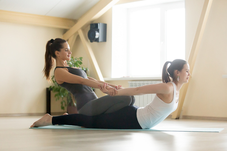 Young beautiful lady beginning yoga practice with private teacher at home, class, working out with professional female yogi instructor. Yoga trainer helps student to do spinal exercise, Locust pose Stockfoto