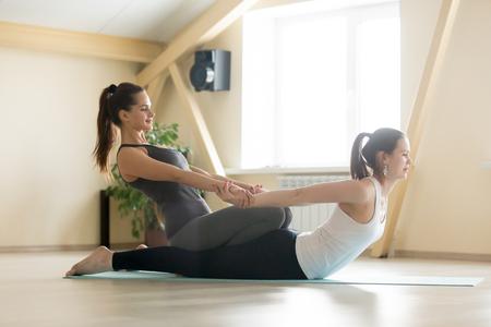 Jonge mooie dame begin yoga praktijk met privéleraar thuis, klasse, uit te werken met professionele vrouwelijke yogi-instructeur. Yoga trainer helpt student om spinale oefeningen te doen, Locust pose Stockfoto - 72110309