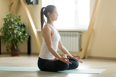 Young attractive woman practicing yoga, sitting in Padmasana exercise, Lotus pose with mudra, working out, wearing sportswear, white tank top, black pants, indoor full length, home interior Stock Photo