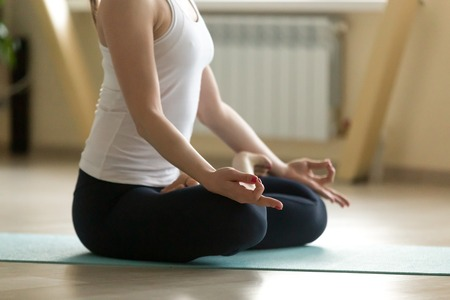 Young attractive happy woman practicing yoga, doing Padmasana exercise, Lotus pose with mudra, working out, wearing sportswear, white tank top, indoor full length, home or sport club, closeup Stock Photo
