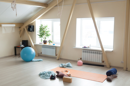 Empty room with fit equipment left after practice. Fitballs, sport mat, yoga props, bolsters, brick, strap, blankets on the floor in loft interior of fitness or yoga club. Healthy lifestyle concept
