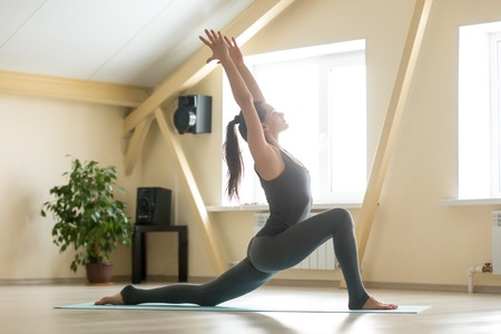 Young attractive woman practicing yoga, standing in anjaneyasana exercise, Horse rider pose, working out, wearing grey sportswear, indoor full length, home interior or sport club background