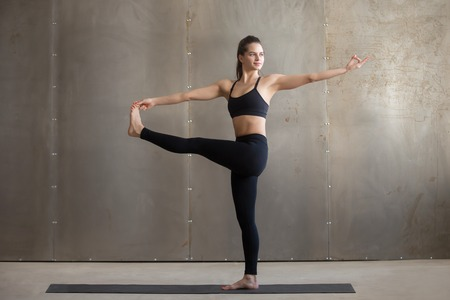 revolved: Young woman practicing yoga, standing in Parivrtta Utthita Hasta Padangusthasana exercise, Twisting Extended Hand to Big Toe pose, working out, wearing black sportswear, cool urban style, full length