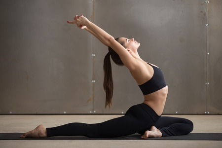 eka: Young attractive woman practicing yoga, stretching in One Legged King Pigeon exercise, Eka Pada Raja Kapotasana pose, working out, wearing black sportswear, cool urban style, full length, grey studio