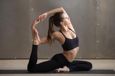pada: Young attractive woman practicing yoga, sitting in Mermaid exercise, Eka Pada Rajakapotasana pose, working out, wearing black sportswear, cool urban style, full length, grey studio background