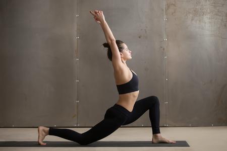 Jonge aantrekkelijke yogi-vrouw die yoga beoefent, staande in anjaneyasana oefening, Paardrijder poseren, uitoefenen van zwarte sportkleding, koele stedelijke stijl, volledige lengte, grijze studio achtergrond, zijaanzicht