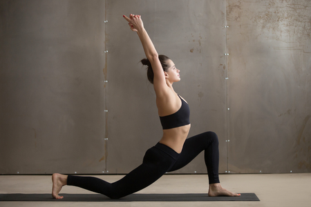 Young attractive yogi woman practicing yoga, standing in anjaneyasana exercise, Horse rider pose, working out wearing black sportswear, cool urban style, full length, grey studio background, side view