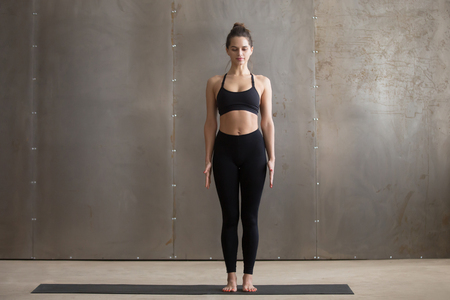 Young attractive yogi woman practicing yoga, standing in Tadasana exercise, mountain pose, working out, wearing black sportswear, cool urban style, full length, grey studio background
