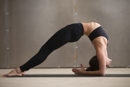 dwi: Young attractive yogi woman practicing yoga, stretching in Elbow Bridge exercise, Dvi Pada Viparita Dandasana pose, working out, wearing black sportswear, cool urban style, full length, grey studio Stock Photo