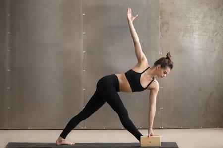 Jonge aantrekkelijke yogi vrouw in zwarte beoefenen van yoga, staande in Utthita Trikonasana oefenen met behulp van blok, uitgebreide driehoek pose, uit te werken, cool stedelijke stijl, volledige lengte, grijze studio achtergrond