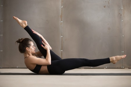 Young attractive woman doing alternate leg stretch, fitness exercise, working out, wearing black sportswear, cool urban style, full length, grey studio background, side view