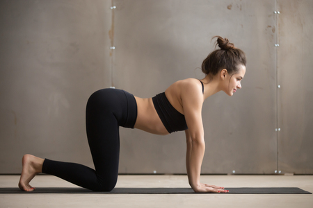 Young attractive woman in black practicing yoga, standing in asana paired with Cat Pose on the exhale, Cow exercise, Bitilasana pose, working out, cool urban style, full length, grey studio background