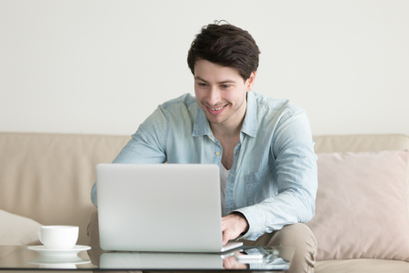 commenting: Young handsome man smiling looking at screen of laptop computer, chatting online, working, texting, commenting social networks. Long distance relationship, technology and lifestyle