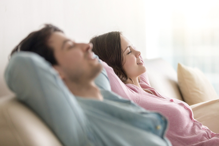 comfortable: Side view of happy young man and woman enjoying sitting on sofa at home, relaxing with eyes closed, resting hands behind the head, recreating, dreaming of vacation, imagining, leisure lazy day