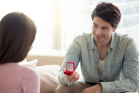 Young guy holding box with engagement ring, making marriage proposal to girlfriend, requesting a hand, indoors. Romantic concept, asking to marry, birthday gift, bride and groom wedding planning
