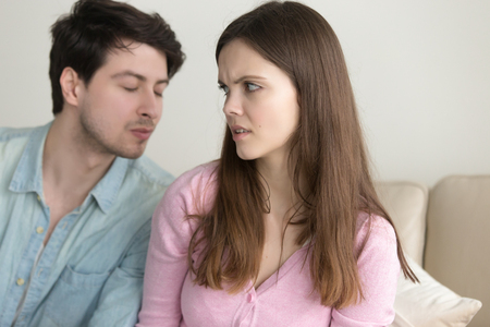 Guy tries to kiss woman, girl dislikes flirting and rejecting man, not interested, saying no, turning away, bad blind date, friend zone, problems in relationships, trying to make peace after quarrel Stock Photo