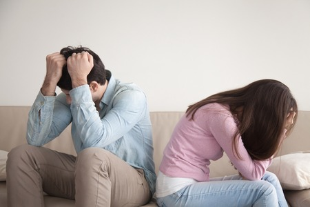 Man and woman feeling stressed and angry at each other, frustrated couple sitting back to back, hands on head, not talking after dispute, teenagers quarrel, family crisis and relationships problems Reklamní fotografie