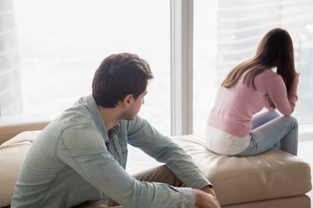 Pareja joven sentado aparte en el interior después de la pelea. Chica ofendida ignorando novio, mirando a otro lado, hombre serio pensando en problemas en las relaciones, conflictos familiares, malentendidos entre los adolescentes